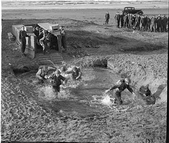 British Commandos - Commandos simulate an amphibious landing by disembarking from a dummy landing craft into a shallow pit filled with water.