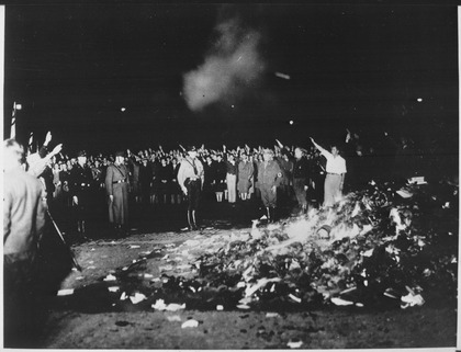 Thousands of books smoulder in a huge bonfire as Germans give the Nazi salute during the wave of book-burnings that... - NARA - 535791.tif
