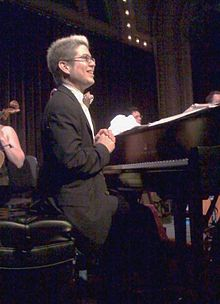 A smiling man with glasses sits at a piano on stage