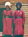 Two Turkmen Men Standing on a Rug, in Front of Yurt.png