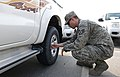 U.S. Air Force Staff Sgt. Dustin Roberts, a 379th Air Expeditionary Wing Public Affairs broadcaster, checks his tires at Al Udeid Air Base, Qatar, Jan. 10, 2014 140110-Z-QD538-007.jpg