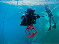 U.S. Navy Diver 2nd Class Andrew Bui, with Space and Naval Warfare Systems Center Pacific, recovers an autonomous underwater vehicle (AUV) built by students from Cornell University after navigating through an 130724-N-TM257-005.jpg