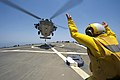 U.S. Navy Lt. j.g. Casey Strouse guides an MH-60S Seahawk helicopter attached to Helicopter Sea Combat Squadron (HSC) 9 on the guided missile destroyer USS Arleigh Burke (DDG 51) in the Persian Gulf June 28 140628-N-WD757-144.jpg