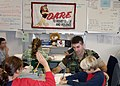 US Navy 031021-N-6362C-001 Master at Arms 2nd Class Aaron M. Hendrickson, Naples area Drug Abuse Resistance Education (DARE) officer, follows along with Justin Goldacker as they work to complete a lesson in the DARE workbook.jpg