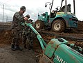US Navy 050215-N-2385R-079 Equipment Operator 3rd Class Robert Chord, assigned to Naval Mobile Construction Battalion Four Zero (NMCB-40), Detachment Sasebo, operates a walk behind roller to compact the gravel over a foundation.jpg