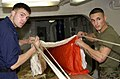 US Navy 050705-N-0361G-031 U.S. Marine Corps Sgt. Juan Franco, right, and Aircrew Survival Equipmentman 3rd Class Brian Hansen perform a canopy inspection on an A-P22P-11 parachute aboard the nuclear-powered aircraft carrier US.jpg