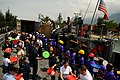 US Navy 080910-N-4515N-084 Service members embarked aboard the amphibious assault ship USS Kearsarge (LHD 3) and citizens of Port au Prince, Haiti load a landing craft utility with supplies for distribution to areas affected by.jpg