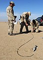 US Navy 111214-N-BA263-610 Chief Explosive Ordnance Disposal Technician Matt Clausen, center, instructs Lt. j.g. Jacob Mello on knot tying techniqu.jpg