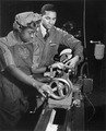 Under the direction of Cecil M. Coles, NYA foreman, Miss Juanita E. Gray learns to operate a lathe machine... - NARA - 535809.tif