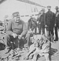 Unidentified man sitting with a dog on a dock, Seattle, ca 1900 (SEATTLE 2841).jpg