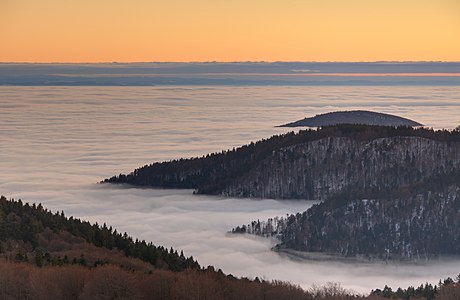 Fog in the valley of the Savoureuse river at the sunset seen from the Ballon d'Alsace (France).