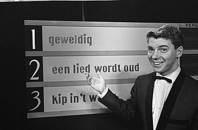 400px-Voorronde_finale_Nationaal_Songfestival_1965%2C_Ronnie_Tober_voor_bord_met_liedjes%2C_Bestanddeelnr_917-4142.jpg