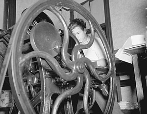 1937 photograph of a printing press with a man operating it