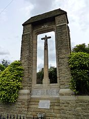 A photograph of a tall stone monument with a crucifix in the centre and a small v-shaped roof supported by two pillars. The names of those who fell in the two world wars are carved in stone at the base of the monument