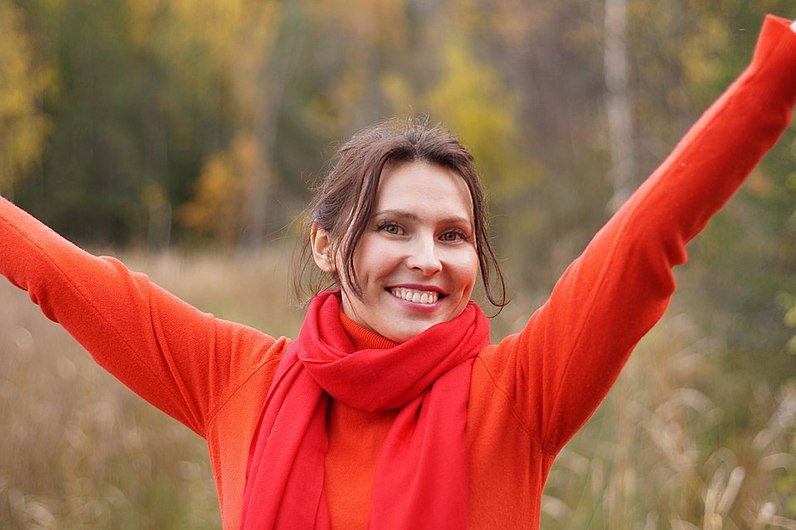 Woman in red sweater with hand in air.jpg