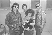 The band standing, with Exene holding a cat