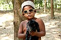 Young boy with goat kid (4432920134).jpg