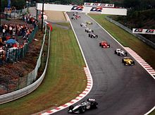 Mika Häkkinen, the first black and silver car, leads a field of ten Formula One cars on a wet track.
