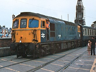 British Rail Class 33 - 33109 arrives at the ferry terminal having negotiated the Weymouth Harbour Tramway on its way to quay in August 1981. Note the bell and beacon warning unit on the cab front and the platform height air brake pipes with two rolled flags wedged behind.