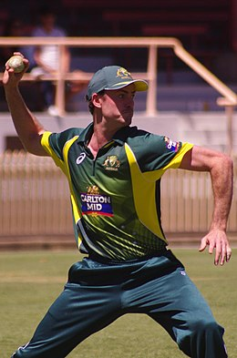 A cricketer dressed in a green uniform with a cap about to throw a cricket ball with his right hand towards the right of the photograph