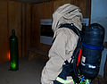 A U.S. troop wearing a chemical suit and an oxygen tank prepares to check a leaking cylinder tank by a wall during joint training at Camp Buehring, Kuwait, Sept 090903-A-PT935-126.jpg