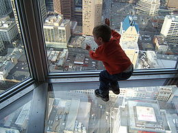 young child leaning against and looking out a skyscraper window on a floor that is also glass