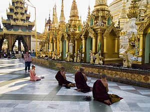 A nun and group of monks praying before idols in Myanmar