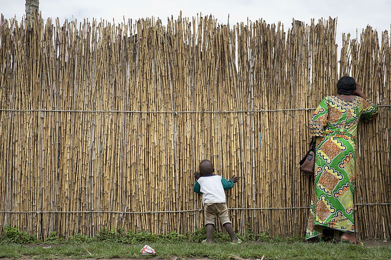 File:A woman and her child look through a bamboo fence.jpg