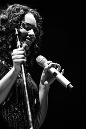 Black-and-white picture of a woman. She holds a microphone with her left hand. She wears a blouse with beads.
