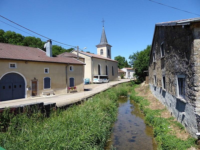 L'Aroffe à Gémonville en Meurthe-et-Moselle avec l'ancien moulin à droite et l'église à l'arrière plan à gauche.