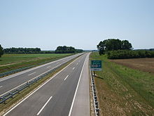 A view of the motorway, a rest area approach traffic sign is located on the right side of the road