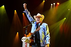 An older man wearing a white cowboy hat and a denim shirt, with a guitar hanging over his shoulder standing at a microphone raising his right fist in the air