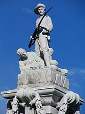 The Boer War Memorial in Dunedin. It is stark white and demonstrates New Zealand's patriotism by showing a man defending his fellow soldier.