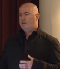 A close-up image of bald man, who looking up behind the camera while talking at a conference.