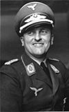 A black-and-white photograph of a smiling man in a military uniform.