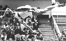 A man in an athletic uniform is diving forward, face-down over a high jump bar. His right leg is extended straight, parallel to the bar, while his left is bent at the knee and is just touching the bar as he leaps over it.