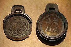 Two circular bronze plates with square handles. The plate on the right is thicker, has four characters embossed into it, and contains a rim around about three fourths of the edge of the plate. The plate on the left is thinner, and contains a rim that, when the two plates were stacked on one another, would perfectly meet the edges of the first plate.