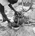COLLECTIE TROPENMUSEUM Een man schenkt water uit een pot in een kalebasschaal TMnr 20010186.jpg