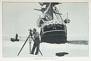 Southern Cross Expedition - Theodolite work in the ice pack, with ship of the Southern Cross Expedition in the background