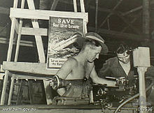 "Black-and-white photograph of two soldiers working with a lathe. A poster behind them depicts a ship with hospital markings sinking by the bow and is captioned with ""SAVE for the brave"" and ""Let us avenge the Nurses""."