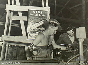 """Black-and-white photograph of two soldiers working with a lathe. A poster behind them depicts a ship with hospital markings sinking by the bow and is captioned with """"SAVE for the brave"""" and """"Let us avenge the Nurses""""."""