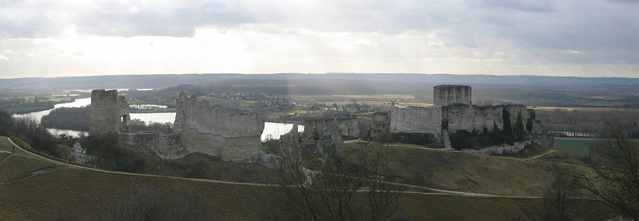 The ruins of a castle in grey limestone dominating the landscape. The River Seine is in the background. The castle's keep protrudes above the walls of the inner bailey on the right, with a bridge leading up to the bailey's entrance. To are ruins of the wall enclosing the outer bailey; a tower stands taller than the ruined walls.