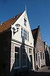 foto van Huis met houten topgevel, voorzien van uitgezaagde windveren en een bewerkte obeliskvormige makelaar