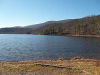 View of the Douthat State Park lake from boat launch area showing blue sky, trees, mountains and water