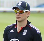 A man wearing an England cricket shirt, a cap and sunglasses