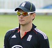 Um homem vestindo uma camisa de críquete da Inglaterra, um boné e óculos de sol