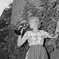 Erika Klein poseert met glas moezelwijn voor een muur begroeid met druiven, Bestanddeelnr 254-4639.jpg