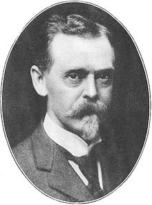 Black-and-white photograph, set in an oval frame, of the head and shoulders of a man of about 55. Dressed formally in a dark suit, dark tie, and white collar, he is looking directly out of the frame. He has dark eyes and dark hair, but his neatly trimmed moustache and goatee are gray.