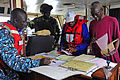 Gambian Navy Leading Seaman Sainey Ngum and Senegalese Navy Staff Sgt. Cheick Sidata Camara look on as Senegal Department of Fisheries Inspector Amadou Bah, center, checks the paperwork of a shrimp boat fishing 120621-N-GN377-003.jpg