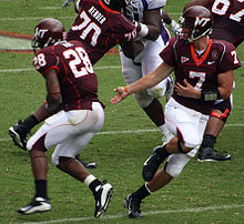 A quarterback hands off the football to his running back. The team is dressed in Chicago maroon and burnt orange jerseys with white pants.